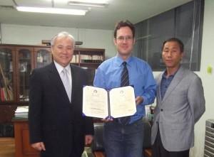 Lee Yongbok (links) und Son Ilhwan (rechts) verleihen Hendrik Rubbeling (Mitte) die Ernennungsurkunde zum Leiter des Taekkyon Zentrum Deutschlands